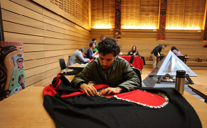 Student Ali Bosworth Rumm sews buttons onto the Big Button Blanket (photo: Michael Glendale, Martlet)
