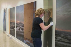 "Emily Geen installing her nominated photo ""A View to Call One's Own"" during the 2015 MFA exhibit"