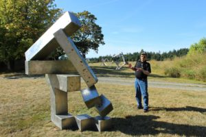 "Jeffrey Rubinoff with his sculpture ""Series 1- 4"" at the Jeffrey Rubinoff sculpture park on Hornby Island (Photo: August 2016. Credit: Michelle Tarnopolsky)"